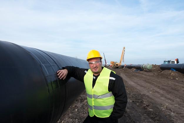 Ritratto di un operaio del giacimento di petrolio in piedi dal tubo del gas al sito in costruzione Foto Gratuite