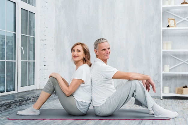 Portrait of a old couple sitting back to back on yoga mat Free Photo