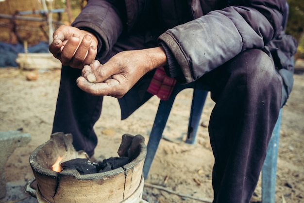 Portrait old man on rural of thailand in winter season with the small fireplace Premium Photo