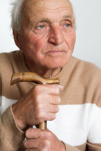 Portrait of an old sad man who put his head on the handle of a wooden cane. Premium Photo