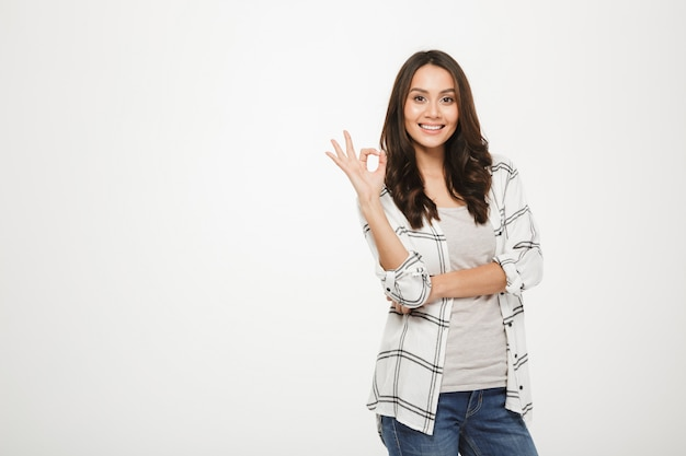 Portrait of optimistic satisfied woman with long brown hair posing on camera and showing ok sign isolated over white Free Photo