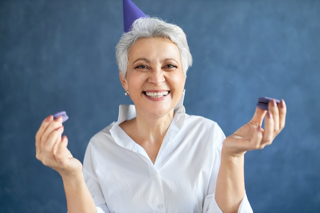 Ritratto di donna di mezza età affascinante felicissima che sorride largamente in possesso di amaretti, gustando un dolce delizioso dessert alla festa di compleanno Foto Gratuite