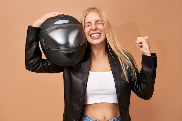 Portrait of overjoyed cheerful young female rider with teeth braces and long straight hair posing isolated in black leather jacket clenching fist after winning race Free Photo