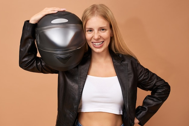 Portrait of overjoyed cheerful young female rider with teeth braces and long straight hair posing isolated in black leather jacket Free Photo