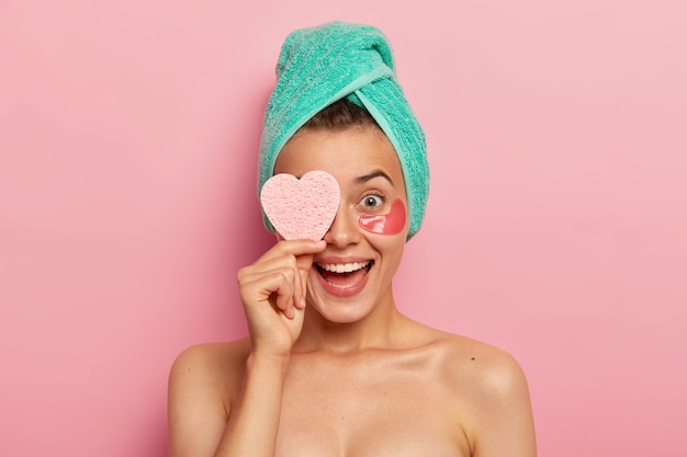 Portrait of overjoyed funny woman keeps cosmetic sponge on eye, laughs sincerely, wears undereye patches, removes wrinkles, cares about skin, has natural beauty Free Photo