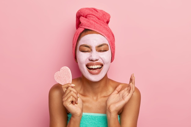 Portrait of overjoyed woman laughs happily, holds cosmetic sponge, raises palm being in high spirit, wears clay mask on face for removing wrinkles and clog pores, stands alone over pink wall Free Photo