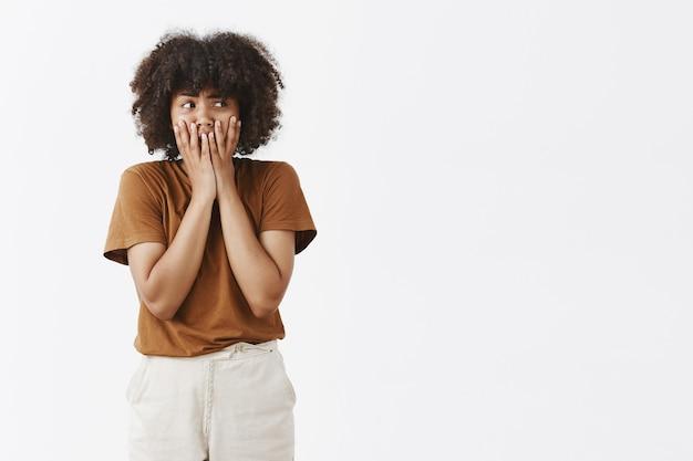 Ritratto di panico timido e insecuto carino modello femminile dalla pelle scura con i capelli ricci che tiene i palmi delle mani sulla bocca per non urlare sensazione di ansia o nervosismo a destra Foto Gratuite