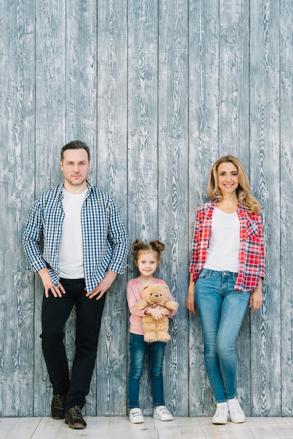 Portrait of parents standing with their daughter holding teddy bear against wooden background Free Photo