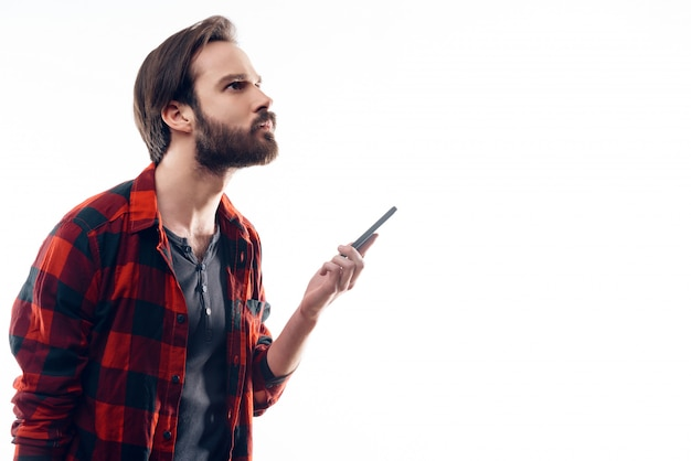 Portrait of pensive man holding phone and looks up Premium Photo