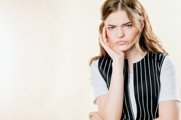 Portrait of a pensive and sullen girl on a light background, a sullen frown Premium Photo
