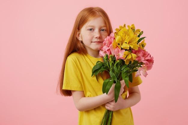 Портрет миниатюрной милой улыбающейся рыжеволосой девушки с веснушками с двумя хвостами, держит букет, носит желтую футболку, стоит на розовом фоне. Бесплатные Фотографии
