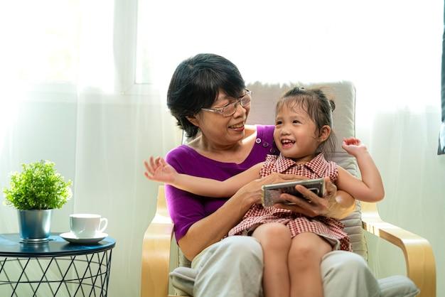 노인 또는 오래 된 아시아 은퇴 여자의 초상화 사진 웃 고 거실에서 안락의 자에 그녀의 손녀와 함께 Siting 동안 스마트 폰에서보고 프리미엄 사진