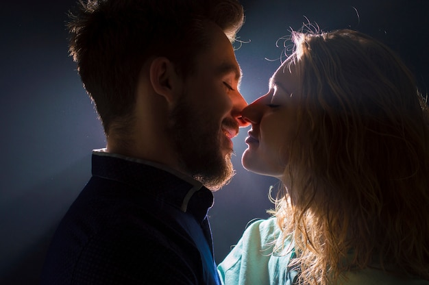 Portrait photo of a sexy young couple in pre kiss in streams of light Premium Photo