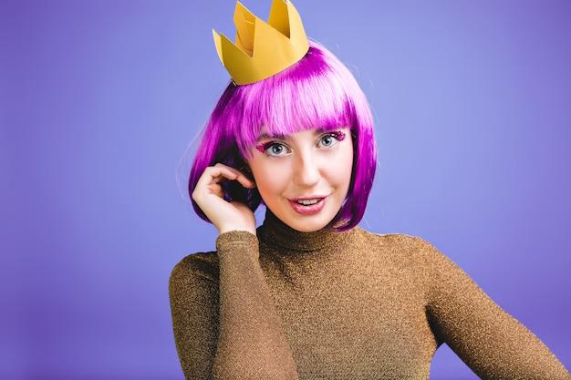 Ritratto di giovane donna allegra con capelli viola tagliati, corona d'oro, vestito di lusso divertendosi. grande festa, carnevale, stile principessa, compleanno, emozioni positive, eccitate. Foto Gratuite