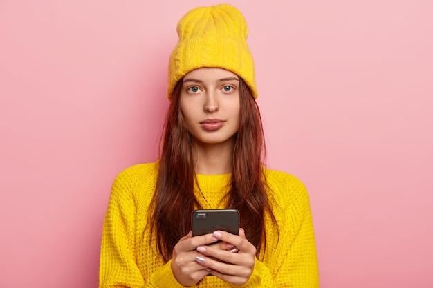 Ritratto di donna dall'aspetto piacevole sembra seriamente, utilizza il moderno telefono cellulare, indossa un cappello giallo e un maglione invernale, posa su uno sfondo roseo, non indossa il trucco Foto Gratuite