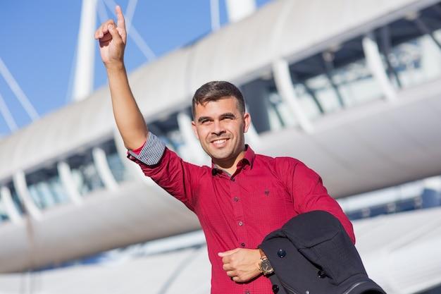 Portrait of positive businessman hailing cab Free Photo