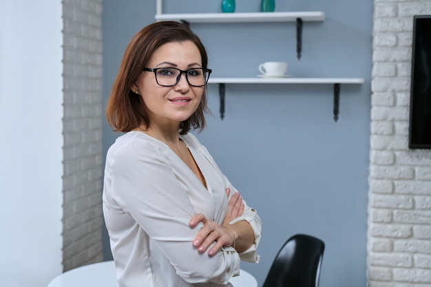 Portrait of positive confident middle aged woman with arms crossed Premium Photo