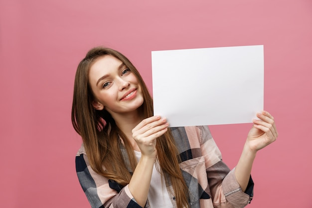 Portrait of positive laughing woman smiling and holding white big mockup poster Premium Photo