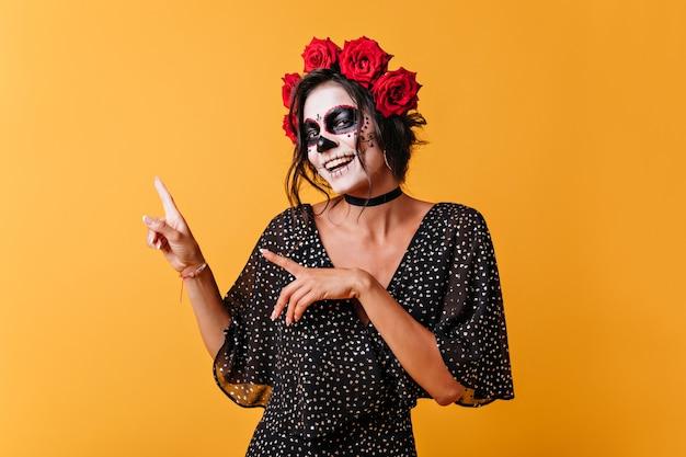 Ritratto di ragazza messicana positiva su sfondo arancione con spazio per il testo. la donna con la maschera del cranio sorride in modo carino e punta le dita verso l'alto. Foto Gratuite