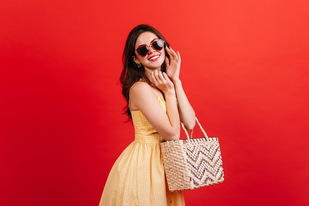 Portrait of positive woman in high spirits posing on red wall. dark-haired lady in bright summer outfit holding beach bag. Free Photo