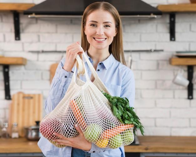 Portrait of positive woman proud of organic vegetables Free Photo