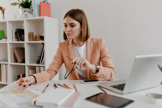Portrait of a positive woman in a stylish business outfit looking at documents on her desktop with interest. Free Photo