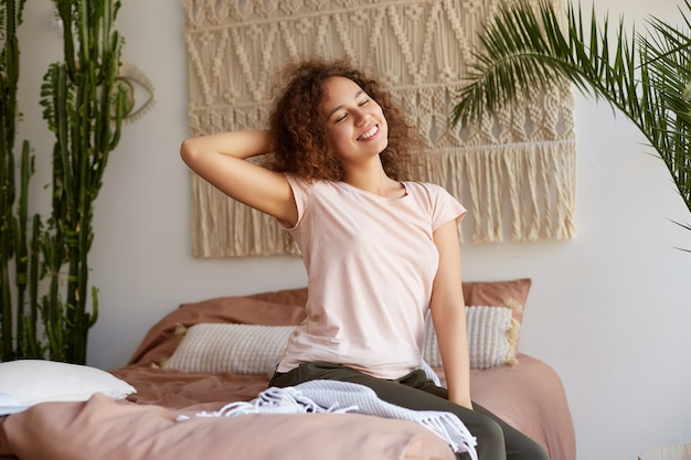 Portrait of positive young curly mulatto girl siting in bed, dressed in pajamas, smiling and enjoying the late sunday morning. Free Photo