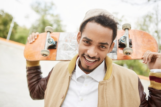 Il ritratto del giovane adolescente positivo pratica lo skateboard all'aperto, ha un'espressione felice Foto Gratuite