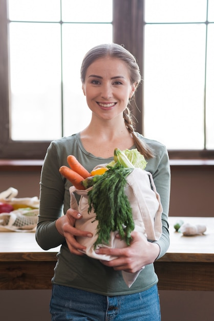 Portrait of positive young woman holding organic vegetables Free Photo