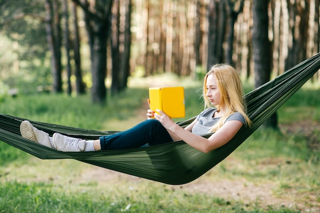 Portrait of preety blonde woman relaxing in hammock in sunny forest and reading e-book. Premium Photo