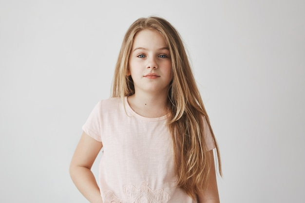 Portrait of pretty blonde girl with long hair in pink pajama. child woke up early, getting ready for school with sleepy expression. Free Photo