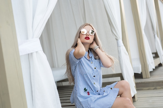 Portrait of pretty blonde girl with long hair posing on the street. she wears blue dress and glasses Premium Photo