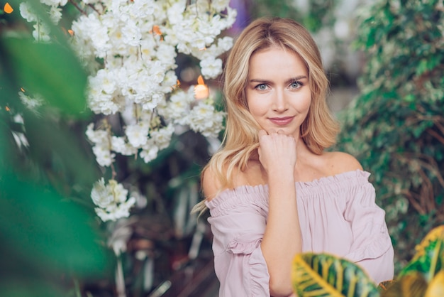 Portrait of pretty blonde young woman standing in lush Free Photo