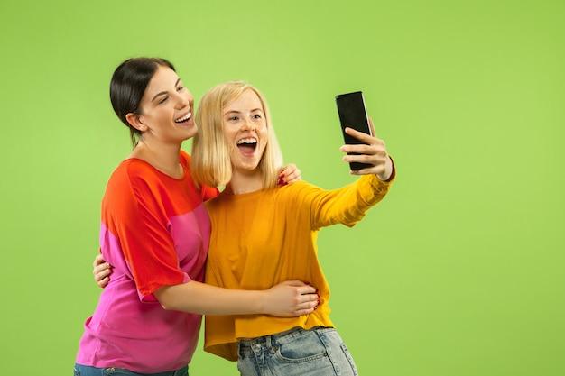 Ritratto di ragazze abbastanza affascinanti in abiti casual isolato sulla parete verde. fidanzate o lesbiche che fanno selfie. concetto di lgbt, uguaglianza, emozioni umane, amore, relazione. Foto Gratuite