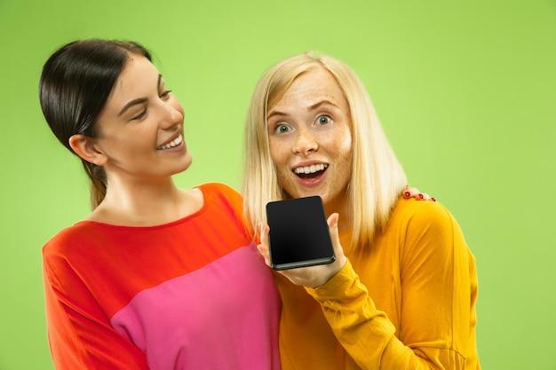 Ritratto di ragazze abbastanza affascinanti in abiti casual isolato sulla parete verde. fidanzate o lesbiche che parlano sullo smartphone. concetto di lgbt, uguaglianza, emozioni umane, amore, relazione. Foto Gratuite