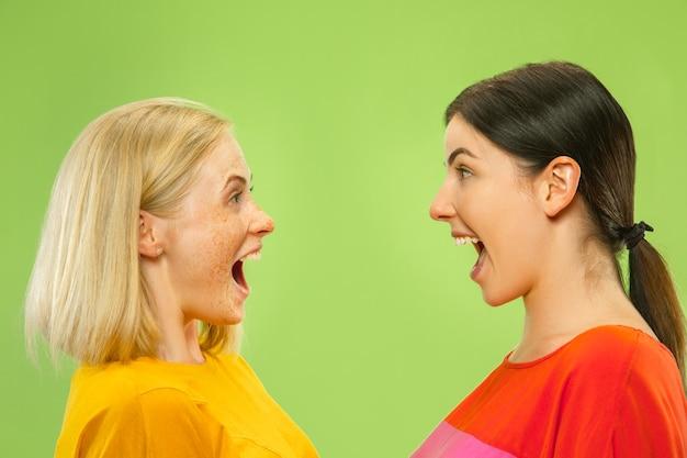Ritratto di ragazze abbastanza affascinanti in abiti casual isolato sulla parete verde. due modelli femminili come fidanzate o lesbiche. concetto di lgbt, uguaglianza, emozioni umane, amore, relazione. Foto Gratuite