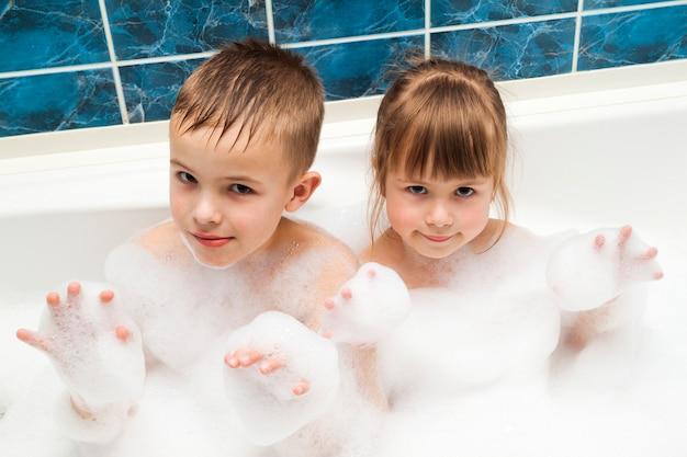 Portrait of pretty children little girl and boy in bath. hygiene concept. Premium Photo