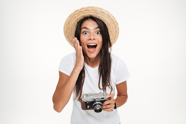 Portrait of pretty excited woman in hat holding a camera Free Photo