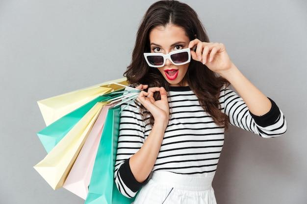 Portrait of a pretty flirty woman holding shopping bags Free Photo