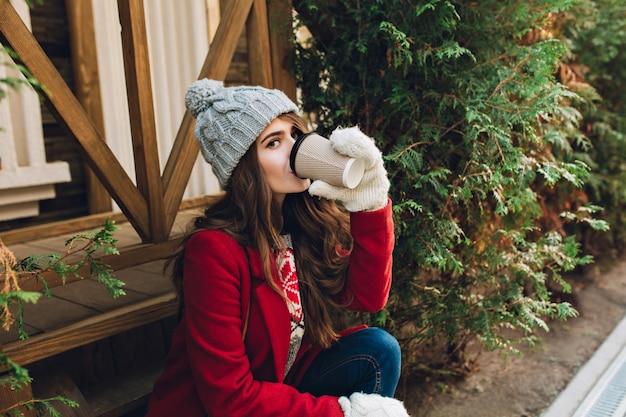 Ragazza graziosa del ritratto con capelli lunghi in cappotto rosso, cappello lavorato a maglia e guanti bianchi che si siedono sulle scale di legno all'aperto. beve caffè e guarda. Foto Gratuite