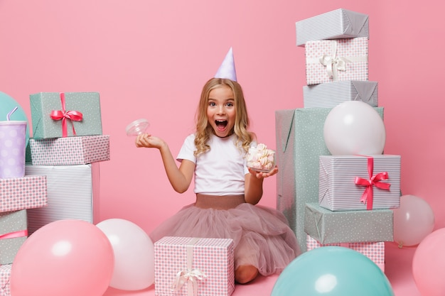 Portrait of a pretty little girl in a birthday hat Free Photo