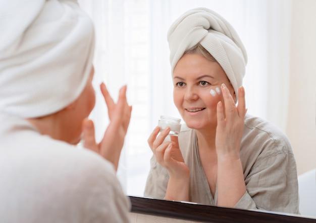 バスルームのスキンケア後自宅で彼女の顔の鏡に手を持つ肖像画かなり年配の女性 Premium写真