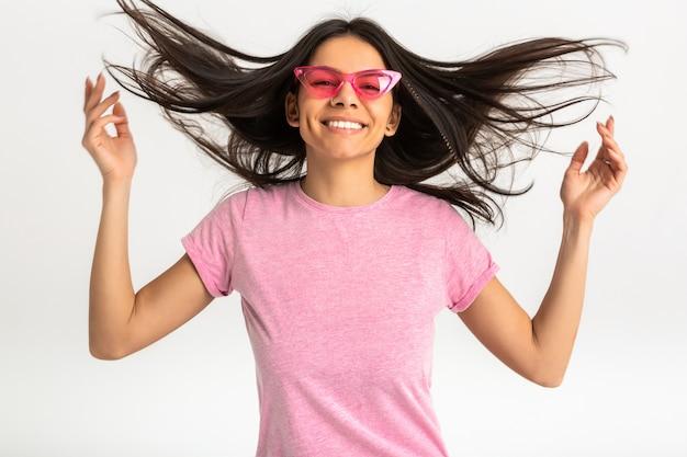 Ritratto di donna emotiva abbastanza sorridente in camicia rosa e occhiali da sole alla moda, denti bianchi, posa positiva isolata, capelli lunghi Foto Gratuite
