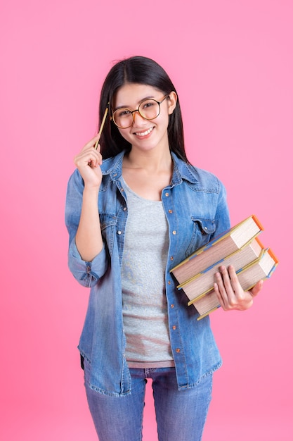 Portrait pretty teenage female holding books in her arm and using pencil on pink, education concept Free Photo