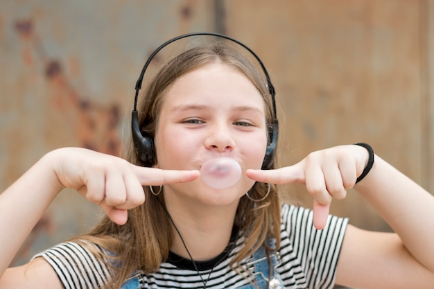 Portrait of pretty teenage girl wearing headphone pointing on bubble gum balloon Free Photo