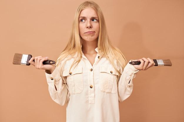 Ritratto di una bella ragazza adolescente con bretelle e capelli lunghi utilizzando strumenti speciali mentre dipingono le pareti interne per proteggerle dai danni causati dall'acqua o dalla corrosione Foto Gratuite