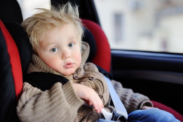 Portrait of pretty toddler boy sitting in car seat. child transportation safety Premium Photo