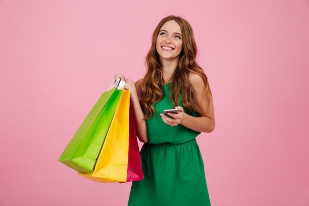 Ritratto di una bella donna in abito tenendo il telefono cellulare Foto Gratuite