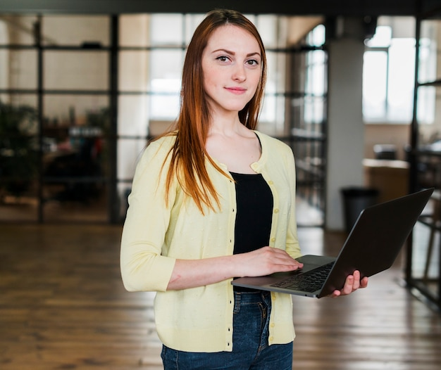 Portrait of pretty woman holding laptop looking at camera Free Photo
