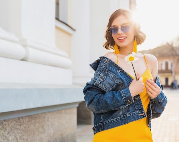 Ritratto di bella donna che indossa occhiali da sole a cuore tenendo il fiore contro il sole, soleggiata giornata estiva, abbigliamento elegante, tendenza della moda, giacca di jeans blu, vestito giallo, orecchini boho hipster eleganti Foto Gratuite